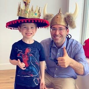 Dr. Noah and child patient wearing crazy hats.