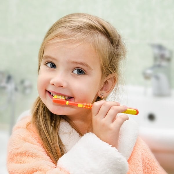 Young child smiling and brushing her teeth.