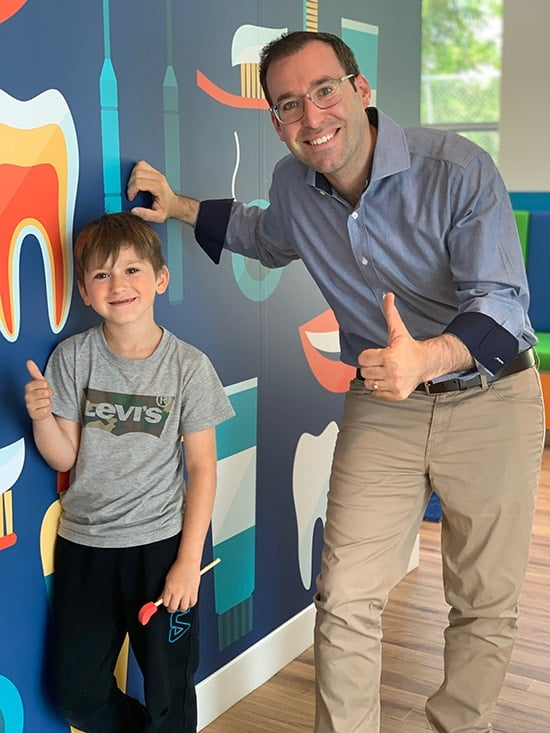 Thumbs Up - Dr. Noah with a child patient.